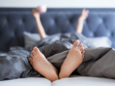 good morning concept - female hands and legs sticking out from the blanket in bedroom